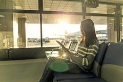 Femme de voyageur de passager dans l'utilisation d'aéroport du comprimé au départ h Image libre de droits