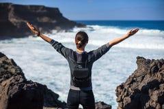 Femme de voyageur de liberté avec les bras augmentés appréciant l'océan Photographie stock