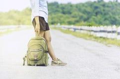 Femme de voyageur se tenant avec le sac à dos appréciant le coucher du soleil sur la crête MOIS Images stock