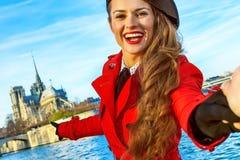 Femme de voyageur tenant la main d'amis et se dirigeant chez Notre Dame Image stock