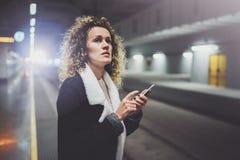 Femme de voyageur textotant un smartphone tandis qu'attend avec une valise dans un aéroport ou une station de train de rail Images libres de droits