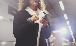 Femme de voyageur textotant un smartphone tandis qu'attend avec une valise dans un aéroport ou une station de train de rail Images stock