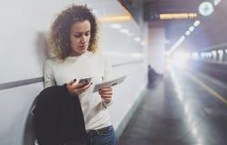 Femme de voyageur textotant un smartphone tandis qu'attend avec une valise dans un aéroport ou une station de train de rail Image stock