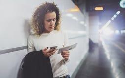 Femme de voyageur textotant un smartphone tandis qu'attend avec une valise dans un aéroport ou une station de train de rail Photo stock