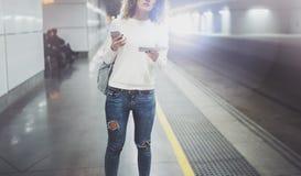 Femme de voyageur textotant un smartphone tandis qu'attend avec une valise dans un aéroport ou une station de train de rail Photographie stock