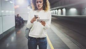 Femme de voyageur textotant un smartphone tandis qu'attend avec une valise dans un aéroport ou une station de train de rail Image libre de droits