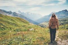 Femme de voyageur trimardant en montagnes Photo stock