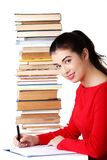 Femme de vue de côté s'asseyant avec la pile de livres Images stock