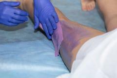 Femme de Waxing Leg Of d'esthéticien avec la bande de cire à la clinique de beauté images libres de droits