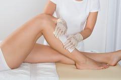 Femme de Waxing Leg Of d'esthéticien Photographie stock