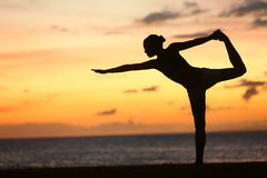 Femme de yoga dans le coucher du soleil serein à la plage faisant la pose Photographie stock