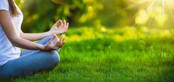 Femme de yoga méditant au coucher du soleil Images stock