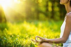 Femme de yoga méditant au coucher du soleil Image stock