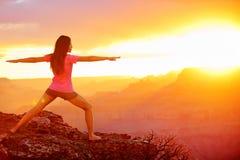 Femme de yoga méditant au coucher du soleil dans Grand Canyon Image stock