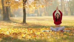 Femme de yoga méditant en Autumn Park banque de vidéos