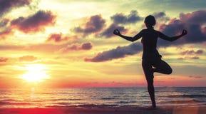 Femme de yoga méditant sur la plage pendant le coucher du soleil Photos stock