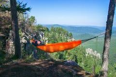 Femme de Yong détendant dans un hamac sur la montagne photos libres de droits