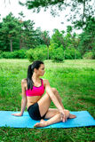 femme de yougn faisant l'exercice de youga extérieur en parc de ville Image stock
