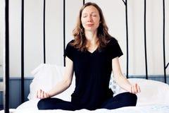Femme de Zen Business faisant la méditation de yoga sur le lit décontracté dans la pose de lotus photos stock