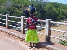 Femme de Zimbabwian sur le pont avec le sac sur sa tête photographie stock libre de droits