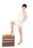 Femme debout et deux oranges sur une boîte en bois Photos stock