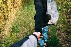 Femme dedans avec les cheveux rouges tenant son ami à la main et le menant au jardin avec des arbres de fleurs de cerisier au lev Photos stock