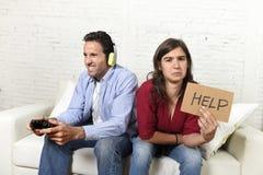 Femme demandant le renversement fâché d'aide tandis que le mari ou l'ami joue des jeux vidéo l'ignorant Image stock