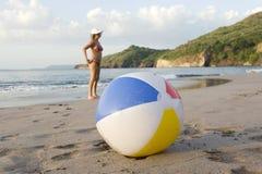Femme derrière la bille de plage colorée sur la plage Photo libre de droits