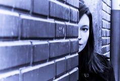 Femme derrière le brickwall photographie stock libre de droits