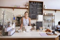 Femme derrière le compteur d'un café regardant à l'appareil-photo Photographie stock