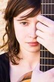 Femme derrière le fretboard de guitare images stock