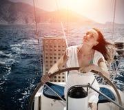Femme derrière le yacht de roue Photos stock