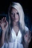 Femme derrière un hublot pluvieux Photos stock