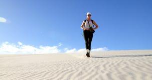 Femme descendant la dune de sable dans le désert 4k banque de vidéos