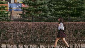 Femme descendant la rue après université La fille chinoise vont avec le sac d'école banque de vidéos