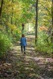 femme descendant la traînée de forêt avec l'appareil-photo dans la lumière d'automne photos stock