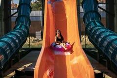 Femme descendant par la glissière en parc d'aqua photo libre de droits
