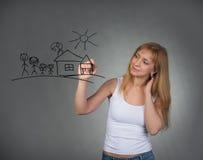 Femme dessinant la famille heureuse et la petite maison avec le stylo sur l'écran Image stock