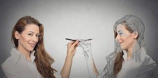 Femme dessinant une photo, croquis d'elle-même photographie stock libre de droits