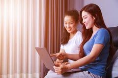 Femme deux à l'aide d'un ordinateur portable sur le sofa dans le salon à la maison Photo stock