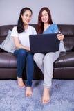 Femme deux à l'aide d'un ordinateur portable sur le sofa dans le salon à la maison Images stock