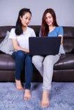 Femme deux à l'aide d'un ordinateur portable sur le sofa dans le salon à la maison Images libres de droits