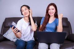 Femme deux à l'aide de l'ordinateur portable et écoutant la musique dans le headph Photos libres de droits