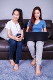 Femme deux à l'aide de l'ordinateur portable et écoutant la musique dans le headph Photo libre de droits