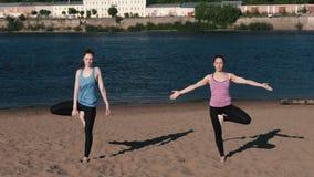 Femme deux étirant le yoga se tenant sur la plage à côté de la rivière dans la ville Belle vue de ville Pose d'équilibre banque de vidéos
