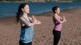 Femme deux étirant le yoga se tenant sur la plage à côté de la rivière dans la ville Belle vue de ville Pose de Namaste banque de vidéos