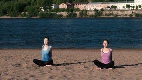 Femme deux étirant le yoga sur la plage par la rivière dans la ville Belle vue de ville Pose de méditation clips vidéos