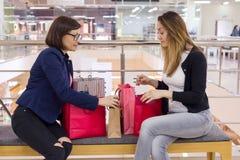 Femme deux après l'achat, regardant des sacs, se reposant Photo stock