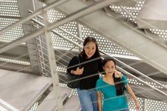Femme deux asiatique heureuse regardant l'appareil-photo et souriant sur la caisse d'escaliers images libres de droits