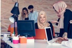 Femme deux avec le hijab travaillant sur l'ordinateur portable dans le bureau Image libre de droits